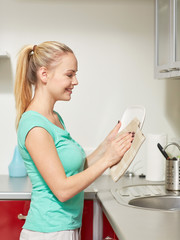 happy woman wiping dishes at home kitchen