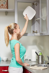 happy woman putting plate to kitchen cabinet