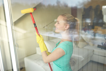happy woman in gloves cleaning window with sponge