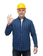 smiling male builder in helmet showing ok sign