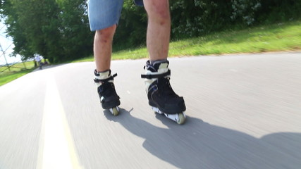 Young man rollerblading in park on a beautiful day, feet going backwards