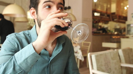 Handsome young man drinking wine in a restaurant