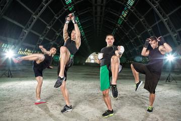 Four men practicing kick box