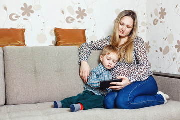 Mom and son sitting on the couch with a tablet PC