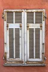 Closed white weathered window shutters on a red wall