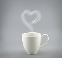 Cup of hot coffee with steam on gray background