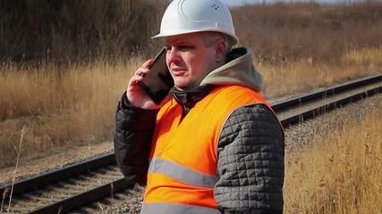 Railway employee talking on cell phone near railway
