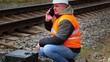 Worker talking on cell phone near railway