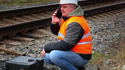 Worker talking on cell phone near railway