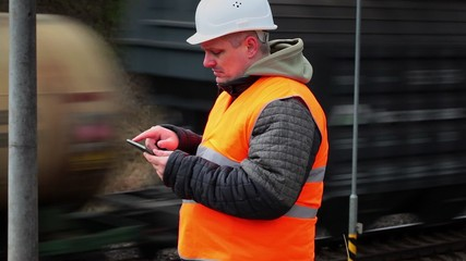 Railway employee with tablet PC near the passing train