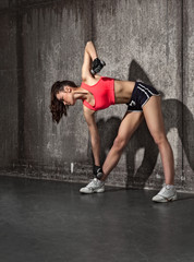 young fit woman lifting dumbbells on dark background