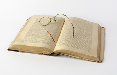Old book and reading glasses on white background