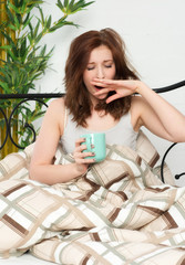 Frau trinkt den ersten Kaffee im Bett