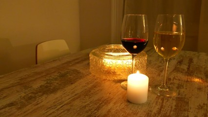Burning candles and two glasses of wine on a table