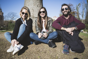 Group of friends two women and one man, sitting on floor in the