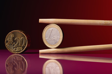 Euro coin with chopstick over red background