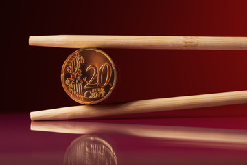 Stack of 20 euro cent coins with chopstick over red background