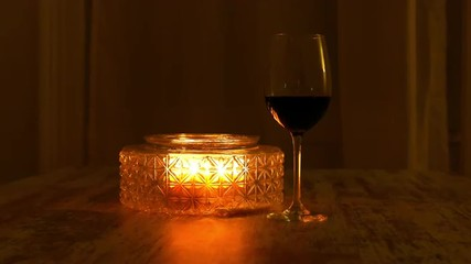 A glass of red wine at candle light
