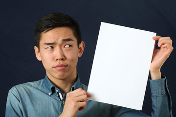 Funny young Asian man showing white copy space page and looking