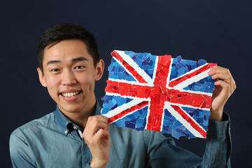 Young Asian student showing UK national flag and looking at came