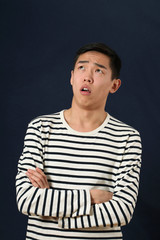 Disappointed young Asian man with crossed hands looking up
