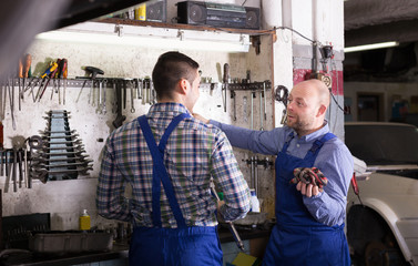Two garage workmen near facilities