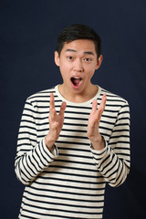 Astonished young Asian man gesturing with two hands and looking