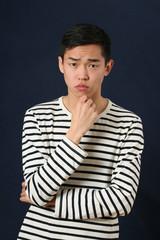 Pensive young Asian man looking at camera