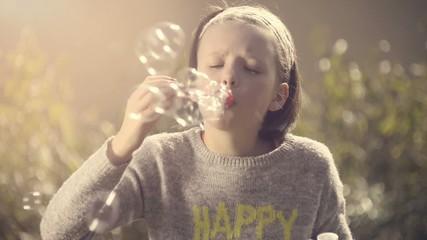 Junges Mädchen pustet Seifenblasen im Garten
