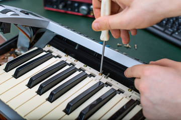Male hand fixing midi keyboard controller.