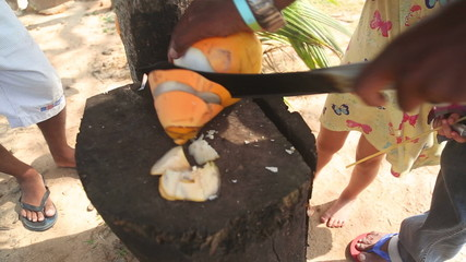Close up view of a local man cutting fresh coconut drink for young child.