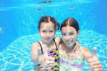 Children swim in pool underwater, girls swimming, kids sport