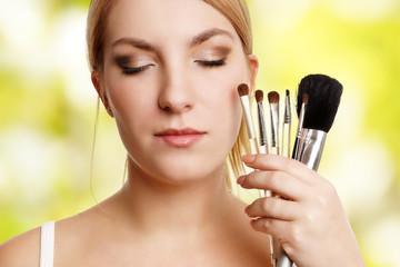 blonde Schönheit hält Makeup Pinsel