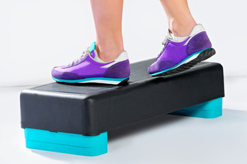 Female feet in violet sneakers do exercise on aerobic step.
