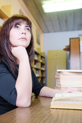Young woman in library in thoughts