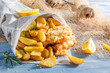 Tasty fish and chips served in paper with lemon - 81253245