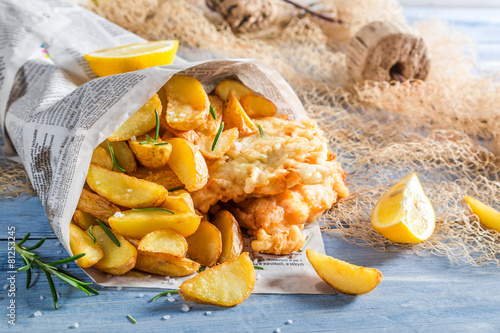 Foto op Plexiglas Vis Tasty fish and chips served in paper with lemon