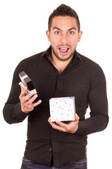 charming young man holding a gift box looking surprised