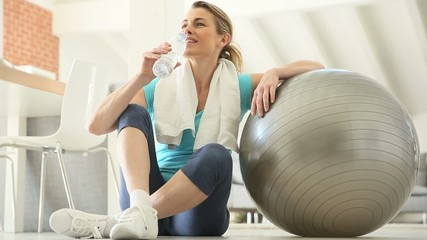 Mature woman drinking water, sitting by fitness ball