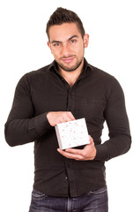 charming young man holding a gift box looking disappointed