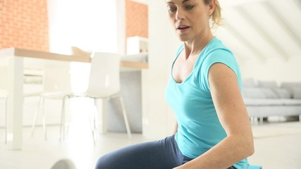 Mature woman at home doing stretching exercises