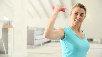 Attractive mature woman lifting dumbbells at home