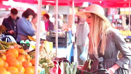Blonde girl with bike is walking at the market, smelling orange