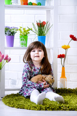 Girl holding a rabbit  flowers around.Easter Spring concep