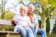 Senioren Paar sitzt im Herbst auf Parkbank