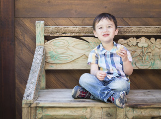 Cute Mixed Race Boy Sitting on Bench Eating Sandwich