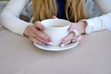 Woman holding white cup of tea or coffe at cafe