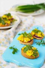 Bruschetta with scrambled eggs and arugula