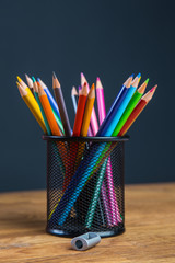 Bunch of color pencils in a stand with sharpener