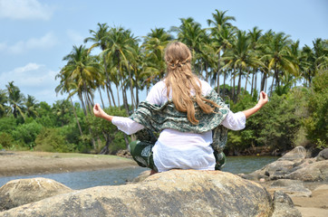Young woman meditating on Agonda beach. Goa, India